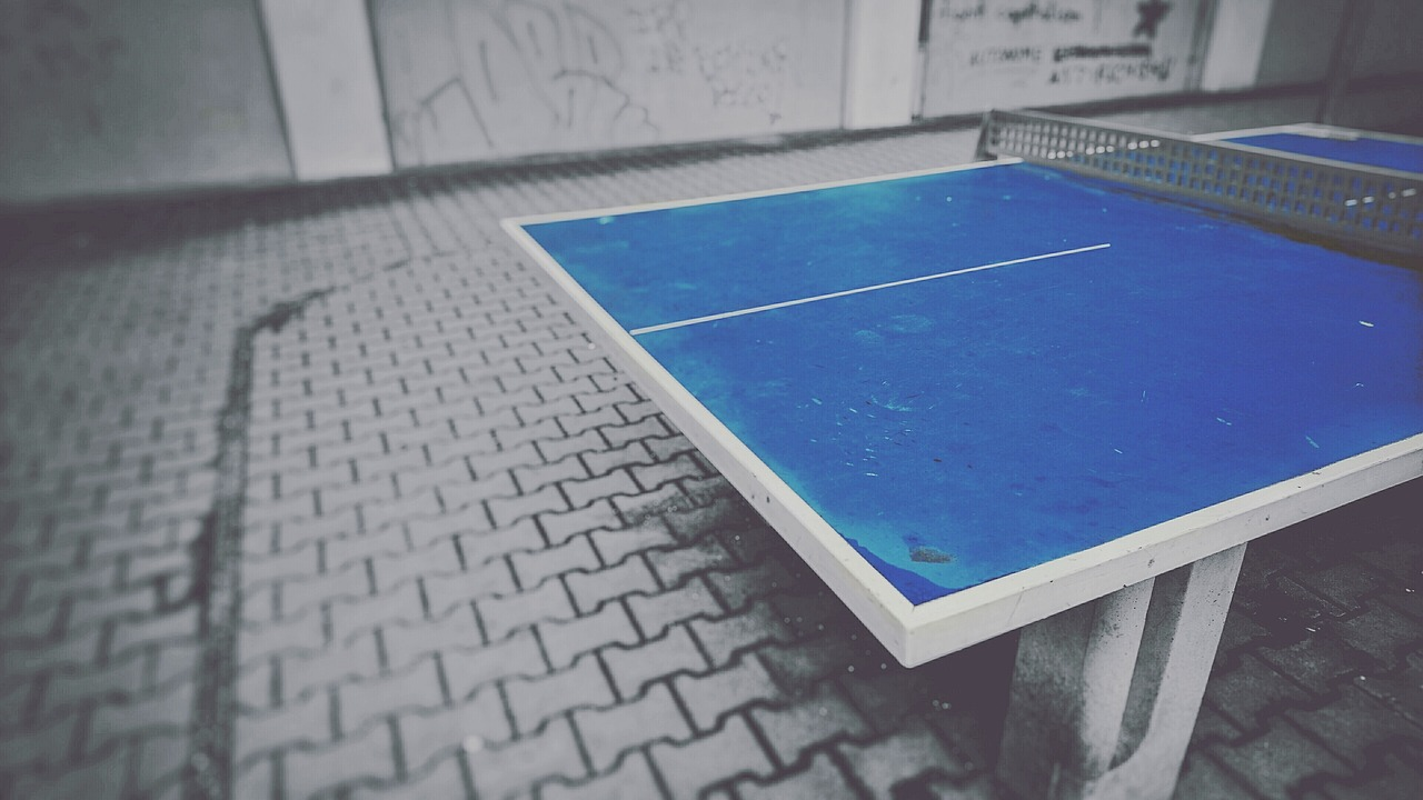A photograph of a ping pong table in a concrete, gritty, city-style backdrop